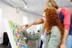 Giovani coppie caucasiche che stanno in una galleria e che contemplano materiale illustrativo fotografia stock libera da diritti