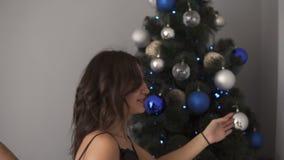 Giovani coppie caucasiche sorridenti che decorano l'albero di abete a casa con le palle colorate blu e d'argento operate Insieme  stock footage