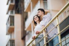 Giovani coppie che abbracciano e che distolgono lo sguardo godenti delle viste al tramonto in un balcone di nuovo hause immagini stock