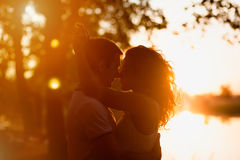 Giovani coppie che abbracciano su un fondo bianco di un tramonto Immagini Stock