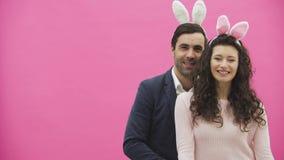 Giovani coppie che abbracciano su un fondo rosa Durante questo tempo, esaminano insieme la macchina fotografica, la ragazza invia video d archivio
