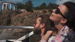 Giovani coppie che accelerano avanti in un motoscafo archivi video