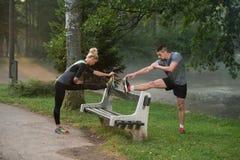 Giovani coppie che allungano prima dell'correre nella foresta boscosa Fotografie Stock