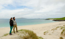 Giovani coppie che ammirano un paesaggio a distanza con la spiaggia di sabbia bianca Fotografie Stock