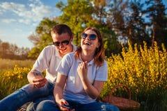 Giovani coppie che appendono in loro telefoni e che ridono fuori Donna ed uomo che relaing dopo avendo picnic al tramonto fotografia stock libera da diritti