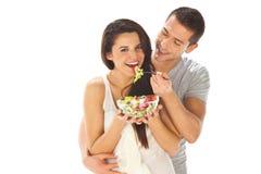 Coppie felici che mangiano insieme insalata su un fondo bianco Immagine Stock