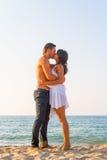 Giovani coppie che baciano alla spiaggia Fotografia Stock Libera da Diritti