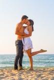 Giovani coppie che baciano alla spiaggia Immagine Stock Libera da Diritti