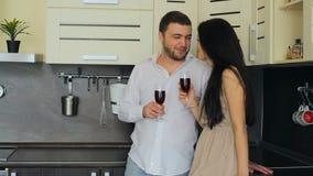 Giovani coppie che bevono vino rosso nella cucina a casa video d archivio