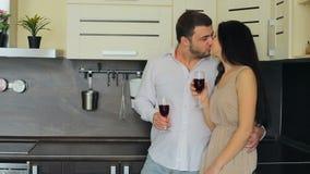 Giovani coppie che bevono vino rosso nella cucina a casa archivi video