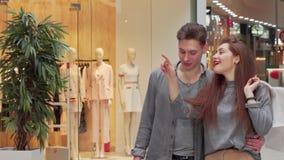 Giovani coppie che camminano al centro commerciale, godente delle vendite stagionali stock footage