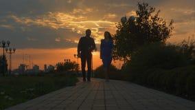 Giovani coppie che camminano alla macchina fotografica Tramonto fotografia stock libera da diritti