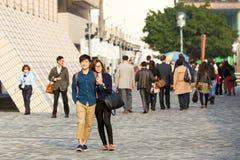 Giovani coppie che camminano alla via ammucchiata che si tiene fotografia stock