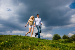 Giovani coppie che camminano attraverso il prato inglese di estate Fotografia Stock
