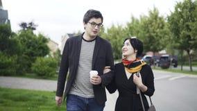 Giovani coppie che camminano e che parlano in una via del sobborgo video d archivio