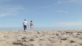 Giovani coppie che camminano insieme e che parlano sulla spiaggia stock footage
