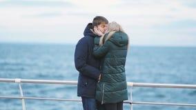 Giovani coppie che camminano su una spiaggia nell'inverno o nell'autunno al giorno freddo stock footage