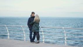 Giovani coppie che camminano su una spiaggia nell'inverno o nell'autunno al giorno freddo archivi video
