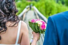 Giovani coppie che camminano sul ponte di legno con il mazzo di nozze Immagine Stock