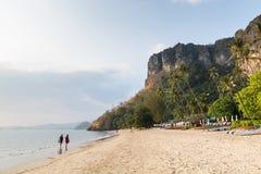 Giovani coppie che camminano sulla spiaggia di Pai Plong al tramonto nella provincia di Krabi, Tailandia immagine stock