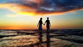 Giovani coppie che camminano sulla spiaggia nelle onde Fotografie Stock Libere da Diritti