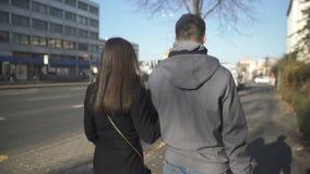 Giovani coppie che camminano sulla via e che guardano indietro, truffatori che lasciano il posto di crimine video d archivio