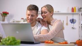 Giovani coppie che cercano le ricette dell'alimento sui siti Web e che ridono, principianti della cucina archivi video