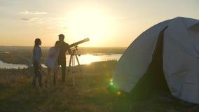 Giovani coppie che chiamano il loro amico ad osservare tramite il telescopio il tramonto sulla collina archivi video