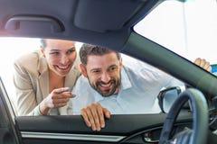 Giovani coppie che comprano un'automobile Immagini Stock Libere da Diritti