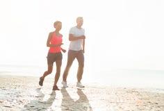 Giovani coppie che corrono insieme accanto all'acqua alla spiaggia Uomo Immagini Stock Libere da Diritti