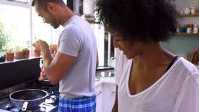 Giovani coppie che cucinano insieme prima colazione in cucina archivi video