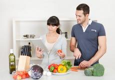 Giovani coppie che cucinano nel paese Immagini Stock