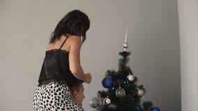 Giovani coppie che decorano insieme un albero di Natale La ragazza castana si siede sulle spalle del suo ragazzo e mette la cima video d archivio
