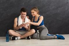 Giovani coppie che discutono piano di allenamento alla palestra Fotografia Stock