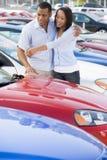 Giovani coppie che esaminano le nuove automobili Immagini Stock