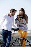 Giovani coppie che esaminano telefono cellulare all'aperto Fotografia Stock Libera da Diritti