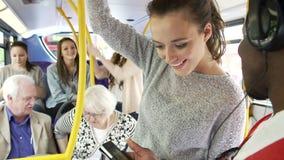 Giovani coppie che esaminano telefono cellulare sul bus ammucchiato archivi video