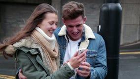 Giovani coppie che esaminano uno smartphone archivi video