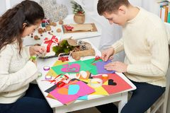Giovani coppie che fanno i cuori dalla carta per il giorno di S. Valentino, la vista superiore - romantica ed il concetto di amor fotografia stock libera da diritti