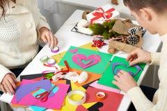 Giovani coppie che fanno i cuori dalla carta per il giorno di S. Valentino, la vista superiore - romantica ed il concetto di amor immagine stock libera da diritti