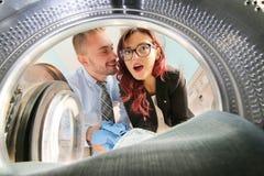 Giovani coppie che fanno lavanderia veduta dalla lavatrice Immagini Stock Libere da Diritti