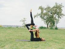 Giovani coppie che fanno posa di yoga dell'uccello di acro Attività moderna di stile di vita sano Immagine Stock