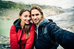 Giovani coppie che fanno un'escursione nelle alpi svizzere, prendenti un Selfie Fotografie Stock