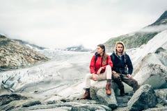 Giovani coppie che fanno un'escursione nelle alpi svizzere, prendenti una rottura Fotografie Stock Libere da Diritti