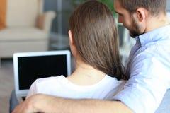 Giovani coppie che fanno una certa spesa online a casa, facendo uso di un computer portatile sul sofà fotografia stock libera da diritti