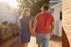 Giovani coppie che fanno una passeggiata nel loro cortile Fotografia Stock Libera da Diritti