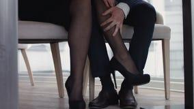 Giovani coppie che flirtano con le gambe al ristorante sotto la tavola Immagine Stock