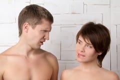 Giovani coppie che flirtano vicino alla parete bianca Immagine Stock