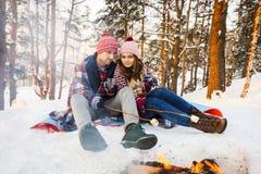 Giovani coppie che friggono le caramelle gommosa e molle ad un fuoco nell'inverno nella foresta Immagine Stock
