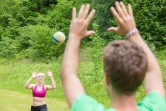 Giovani coppie che giocano pallavolo in parco Immagine Stock